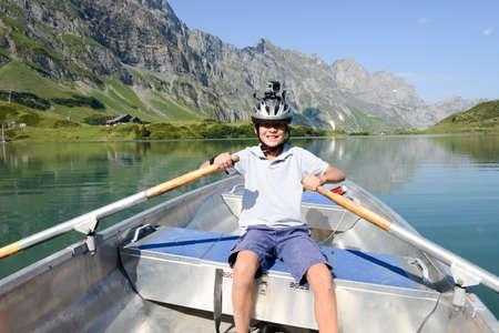 Engelberg, Zwitserland - 13 augustus 2015: Boy roeien op een roeiboot op het meer Truebsee over Engelberg op de Zwitserse Alpen