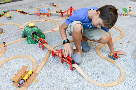 wood railroads: Lugano, Switzerland - 29 August 2015: boy playing with a wooden train set on a garden Editorial