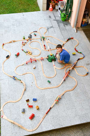 wood railroad: Lugano, Switzerland - 29 August 2015: boy playing with a wooden train set on a garden Editorial