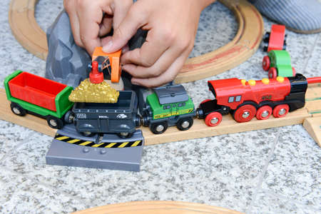 wooden toy: Lugano, Switzerland - 29 August 2015: boy playing with a wooden train set on a garden Stock Photo
