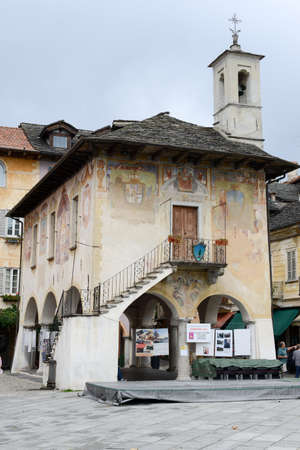 orta: Orta, Italy - 5 September 2015: People visiting on walking the Palace of the Community or Broletto at the main square of Orta on Italy Editorial