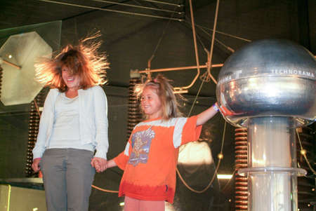 popular science: Winterthur, Switzerland - 13 april 2007: girls playing with the Van Der Graaf generator of the Swiss Science Center Technorama at Winterthur, Switzerland