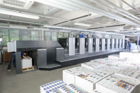 Lugano, Switzerland - 27 May 2013: people working at an offset printing machine at Lugano on Switzerland