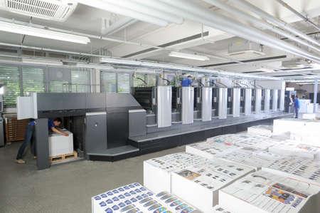 Lugano, Switzerland - 27 May 2013: people working at an offset printing machine at Lugano on Switzerland