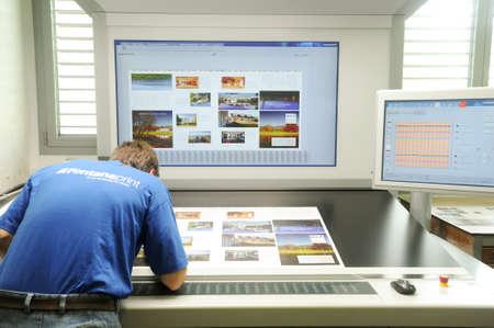 Lugano, Switzerland - 29 May 2013: Printer checking a print run at table
