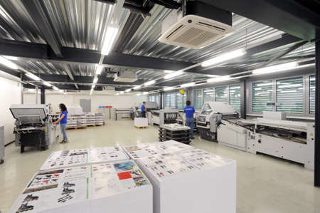 lithograph: Lugano, Switzerland - 29 May 2013: people working at offset printing machines at Lugano on Switzerland Editorial