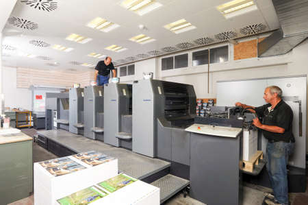 printing out: Bern, Switzerland - 19 september 2013: people working at an offset printing machine at Bern on Switzerland
