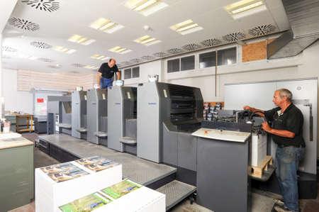 Bern, Switzerland - 19 september 2013: people working at an offset printing machine at Bern on Switzerland
