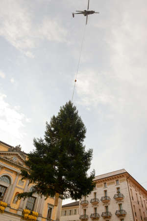 settles: Lugano, Switzerland - 20 november 2015: helicopter settles a Christmas tree in the central square of Lugano on Switzerland