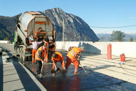 asphalting: Melide, Switzerland - 12 november 2009: Workers and vehicles during the asphalting of the highway at Melide on Switzerland Editorial