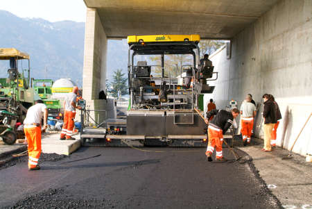 asphalting: Melide, Switzerland - 30 october 2009: Workers and vehicles during the asphalting of the highway at Melide on Switzerland