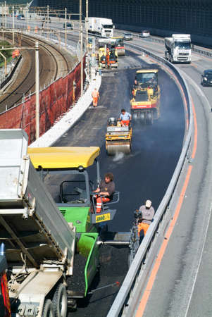 Melide, Switzerland - 29 september 2010: Workers and vehicles during the asphalting of the highway at Melide on Switzerland