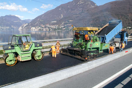 asphalting: Melide, Switzerland - 8 March 2007: Workers and vehicles during the asphalting of the highway at Melide on Switzerland