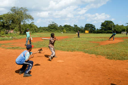 Las Gasleras, Dominican Republic - 24 january 2002: Boys playing baseball on a field at Las Galeras on Dominican Republic