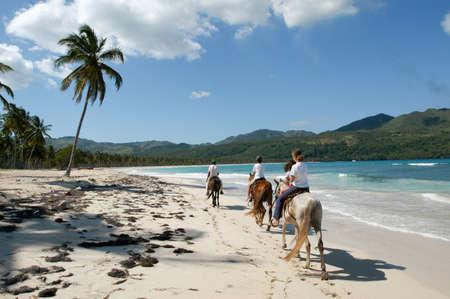 Las Galeras, Dominican Republic - 25 january 2002: people riding horses on the beach of Rincon near Las Galeras on Dominican Republic
