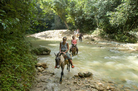 limon: Las Terrenas, Dominican Republic - 22 january 2002: People riding horses on the tourist trip to the waterfall of El Limon in the Dominican Republic