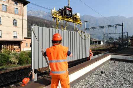 Capolago, Switzerland - 13 march 2012: Workers during the installation of noise barriers on the railway at Capolago on Switzerland Editorial