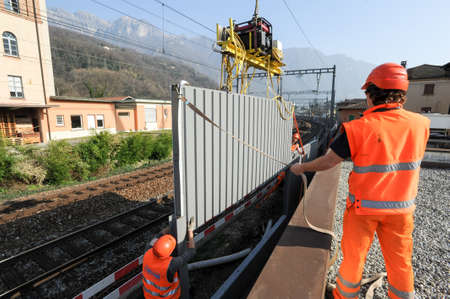 disturbance: Capolago, Switzerland - 13 march 2012: Workers during the installation of noise barriers on the railway at Capolago on Switzerland Editorial