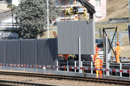Capolago, Switzerland - 24 february 2012: Workers during the installation of noise barriers on the railway at Capolago on Switzerland