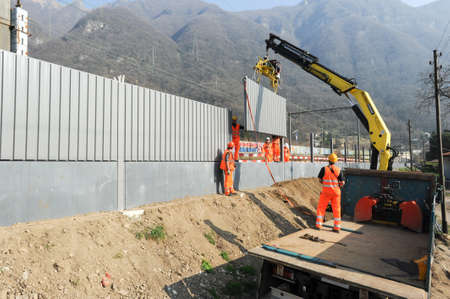 disturbance: Capolago, Switzerland - 14 march 2012: Workers during the installation of noise barriers on the railway at Capolago on Switzerland