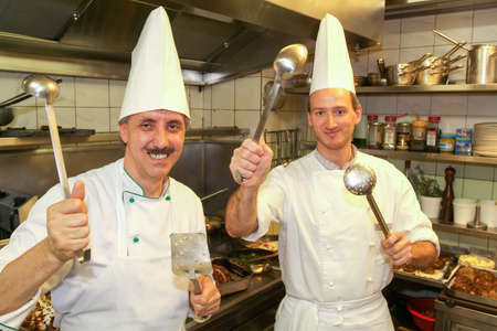 ladles: Lugano, Switzerland - 12 May 2006: two cooks with spoons and ladles in them hands on the kitchen of a restaurant