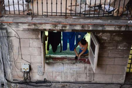 vieja: Havana, Cuba - 27 January 2016: Woman extending the clothes at the window of her house at the neighborhood of Habana Vieja in Havana on Cuba