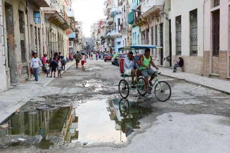 vieja: Havana, Cuba - 7 January 2016: people on a taxi bike at the neighborhood of Habana Vieja in Havana on Cuba
