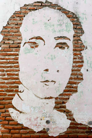 solidity: Artwork face on a brick wall