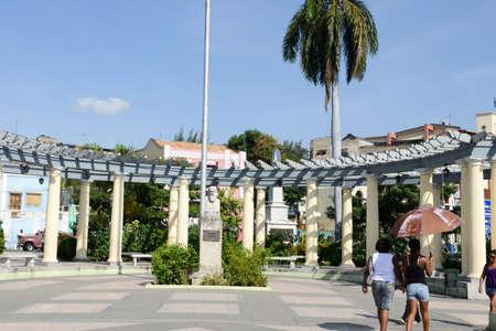 Santiago de Cuba, Cuba - 13 january 2016: people walking in front of Camillo Cienfuegos monument on Marte square at Santiago de Cuba Editorial