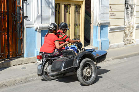 sidecar: Santiago de Cuba, Cuba - 14 january 2016: people driving a sidecar bike at Santiago de Cuba, Cuba