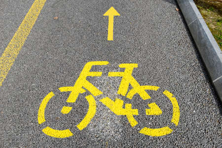 road cycling: Yellow arrows and bicycle sign of a cycling path on the road
