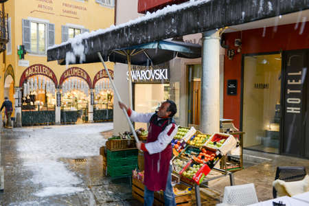 Lugano, Swizerland - 5 march 2016: man is shaking the tent of his shop to remove the accumulated snow in the old part of Lugano in Switzerland