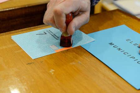 encuestando: Lugano, Switzerland - 11 april 2016: Hand  validating a voting ballot at the municipal election of Lugano on Switzerland