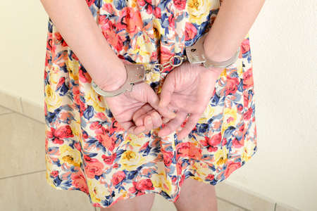woman in handcuffs: Arrested woman in handcuffs behind her back