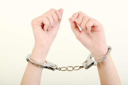 woman in handcuffs: Hands of a woman with handcuffs on a white background
