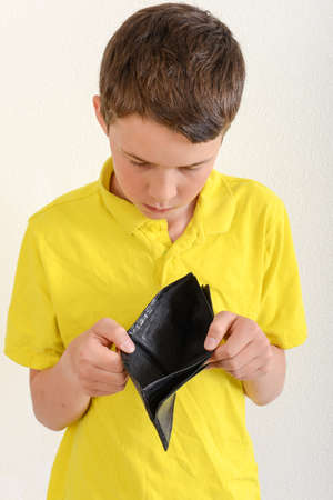 Boy showing empty pockets without money