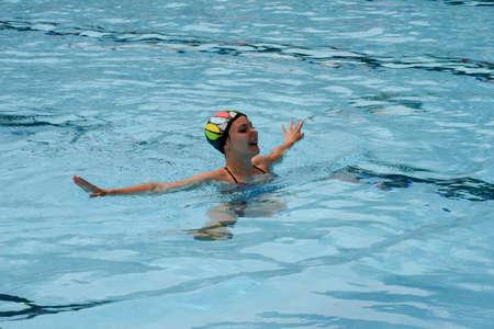 nataci�n sincronizada: Massagno, Suiza - 12 de junio 2016 - ni�a en una piscina practicando la nataci�n sincronizada Editorial