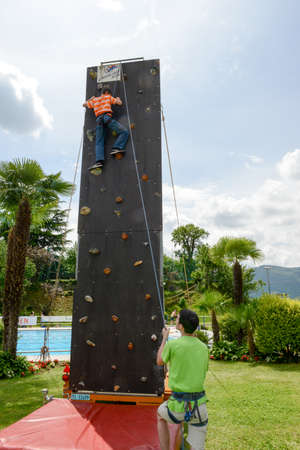 scaling: Massagno, Switzerland - 12 June 2016 - Effort of a boy in climbing a wall to reach the top