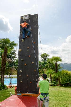 Massagno, Switzerland - 12 June 2016 - Effort of a boy in climbing a wall to reach the top
