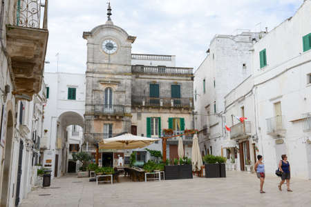 view of a wooden doorway: Cisternino, Italy - 25 June 2016: people walking on the main square of Cisternino on Puglia, Italy