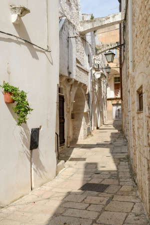 view of a wooden doorway: Narrow alley of Cisternino in Puglia on Italy
