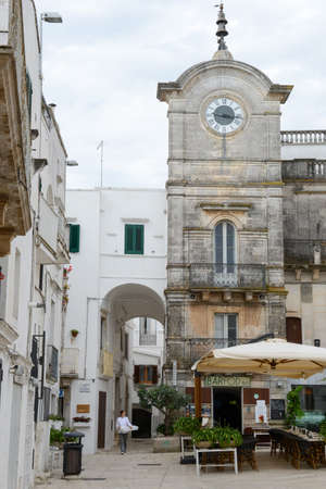 view of a wooden doorway: Cisternino, Italy - 25 June 2016: woman walking on the main square of Cisternino on Puglia, Italy
