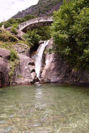Santa Petronilla waterfalls with roman bridge in Biasca, Cantone Ticino, Switzerland