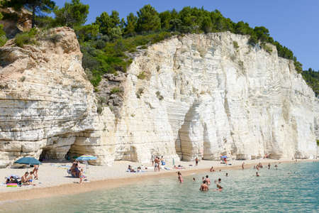 gargano: Vieste, Italy - 30 June 2016: tourists sunbathing and swimming at the beach of Vignanotica on the coast of Gargano National park on Puglia, Italy Editorial