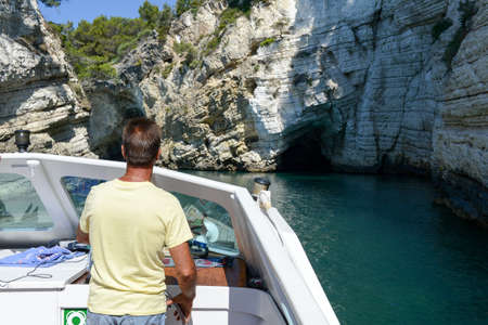 gargano: Vieste, Italy - 30 June 2016: capitain of a touristic boat entering a cave at the coast of Gargano National park on Puglia, Italy