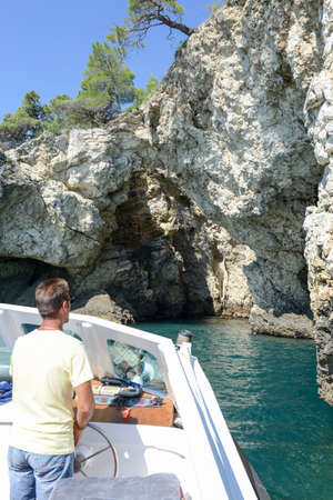 Vieste, Italy - 30 June 2016: capitain of a touristic boat entering a cave at the coast of Gargano National park on Puglia, Italy
