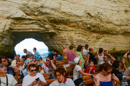 gargano: Vieste, Italy - 30 June 2016: tourists visiting on a boat a cave on the coast of Gargano National park on Puglia, Italy