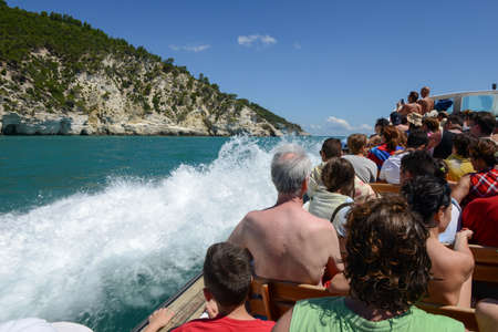 gargano: Vieste, Italy - 30 June 2016: tourists visiting on a boat the coast of Gargano National park on Puglia, Italy