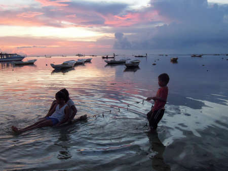 nusa: Nusa Lembongan, Indonesia - 13 February 2013: Children playing at the beach on a colorful sunset in Nusa Lembongan, Indonesia