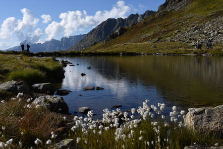 Susten pass, Switzerland - people speaking on the lakeshore at Susten pass on the Swiss alps